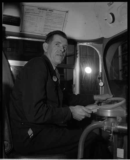 VPL #43418, Province Newspaper, September 16, 1955, Portrait of a bus driver in the driver's seat
